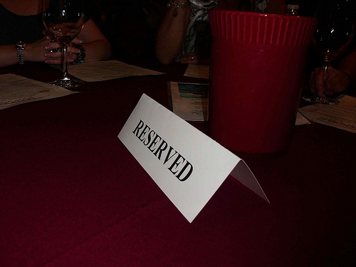 "a table with a sign on it that says ""reserved."" next t the sign there is a red cup."