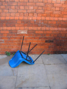 a blue plastic chair that's tipped over on the ground in front of a brick wall