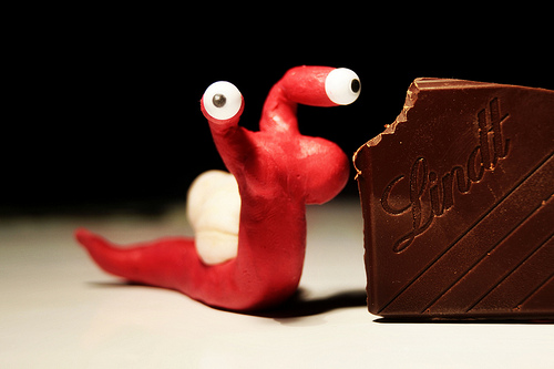 a small red clay slug sculpture positioned next to a chocolate bar with a small bite out of the corner