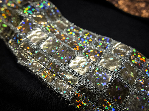 A strip of silver fabric that has shiny iridescent rainbow colors - it appears to be a belt