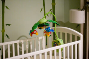 a white crib with a colorful baby mobile toy
