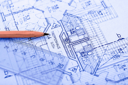 a closeup of building blueprints with a pencil and a ruler in the frame