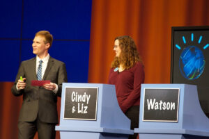 """A game show set. There is a host in a sut and tie and a contestant to his right in a burgundy shirt and black pants. Her team podium reads """"Cindy & Liz."""" The podium to her right reads """"Watson"""""""