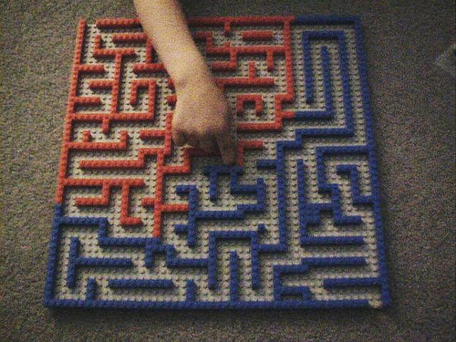 an elaborate maze like labyrinth constructed of half blue and half red legos. A hand is pointing to the center of the maze.