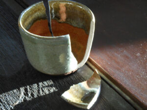 a photograph of a broken cup sitting on a table
