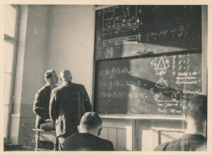 an old photo in which a professor and student stand next to a chalkboard covered with equations and diagrams. The backs of 2 students' heads are visible.