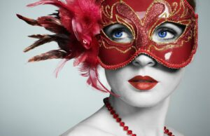 a person with white skin, blue eyes, and red lipstick wearing a red and gold mask with feathers and a red beaded necklace