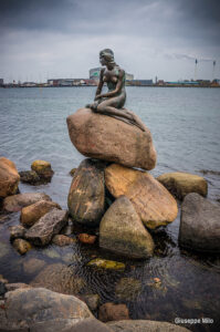 statue of the little mermaid sitting on some rocks by a body of water - this is The Little Mermaid statue in Copenhagen