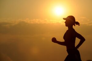the silhouette of a runner who is wearing a visor running in front of a background of a very yellow sunny sky with many clouds