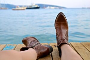 a picture of someone's legs and feet as they lie on a wharf next to a harbor. The feet are wearing brown boots.