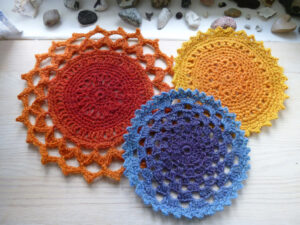 3 crocheted coasters, one large orange, one medium blue, and one small yellow
