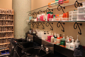 a beauty salon with hair sinks and shelves loaded with products