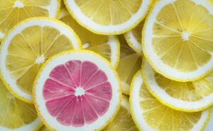 a bunch of lemons slice stacked on top of each other in an overlapping way so you can see many of them. One slice near the bottom right corner has pink flesh inside instead of yellow and sticks out dramatically