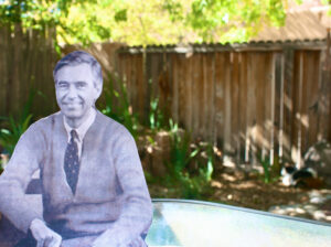 what appears to be a black and white cut out of a photograph of Fred Rogers superimposed on a color photo of someone's back yard patio, complete with greenery and tall wooden fence