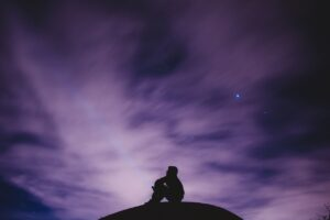 the shadowy form of a person sitting on a hill under a purplish night sky full of stars