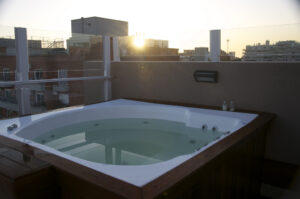 a picture of a hot tub on a rooftop with a sun setting in the background