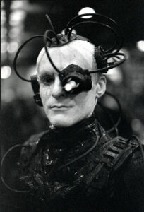 a black and white photo of a member of the Borg. The Borg has a bald head and is wearing a body suit as well as an apparatus with lots of wires coming out of their head