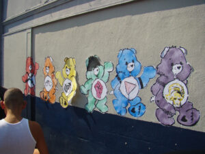 6 rainbow Care Bear paper cutouts pasted onto a wall. They are red, orange, yellow, green, blue, and purple (left to right). They are posed in a variety of poses. Their insignias on their tummies are (left to rigth): A bondage harness, a pair of handcuffs, a pig face, a clenched fist, a pink triangle, and the face of a person with dangly earrings and a blond updo