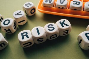 """a bunch of letter blocks from the game Boggle. Located near the center of the photo is 4 blocks spelling out """"risk."""""""