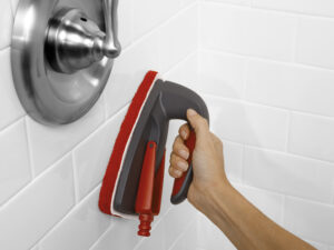 a hand holding a scrubber, scrubbing a shower wall that already appears to be clean
