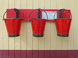 3 red buckets hanging in a row on a red rack with metal hooks
