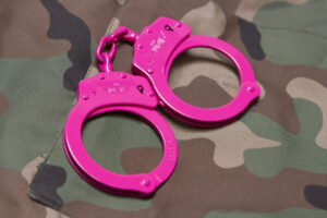 bright pink handcuffs on a camo background