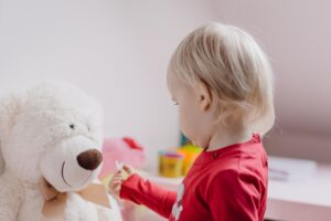 a child with short blond hair who is looking at their white stuffed teddy bear