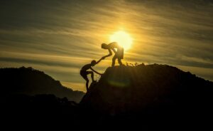 a picture of two silhouettes with the sun behind them. One person is standing on top of the hill and they are holding the hand of the person halfway up the slope, helping them climb.
