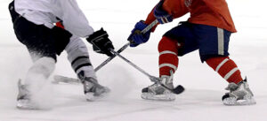 two hockey players, one in a white jersey, one in a red jersey, shot from the shoulders down. Their sticks are crossed.