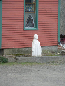a photograph of a statue of Lot's wife turned to salt. The statue is in front of a reddish building with green trim