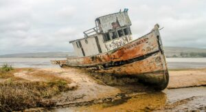 """A wrecked ship on shore. The words """"Point Reyes"""" are on the front of the ship."""