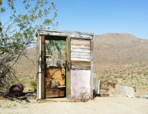a busted up outhouse in the mojave desert