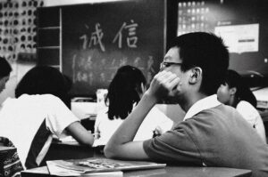a black and white photo of a bunch of kids sitting in a classroom
