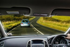 the view of a road from inside of one car following another