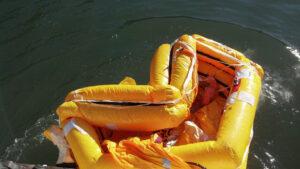an orange life raft in pretty bad shape