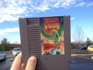 a picture of someone holding up the old Nintendo cartridge of Dragon Warrior in their hand as they stand in what appears to be a parking lot