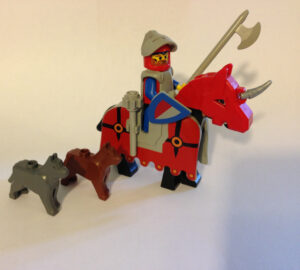 a Lego knight riding a Lego unicorn who seems to have a couple of Lego wolves by their side