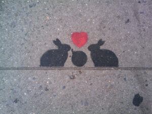 It's a stencil painted onto concrete. Within the stenciled image are two bunnies that have a bomb between them with a heart over it