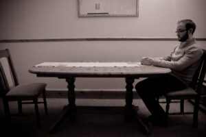 a black and white photo of someone sitting alone at a table