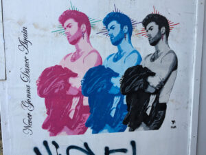 This is street art featuring 3 painted portraits of George Michael side by side, in 3 different colors (magenta, blue, black)