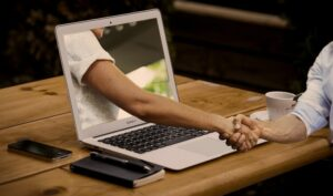 a person pictured on a laptop reaches out of the laptop and shakes hands with the person on the other side