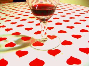 a white tablecloth with many red hearts on it. a glass of red liquid is sitting atop it.