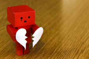 a photo of a red block person with a tear coming out of their eye. They are standing on a wooden table and holding two pieces of a broken heart