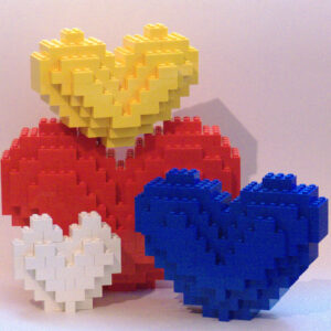 an assortment of 4 various-sized Lego hearts. Their colors: white, red, yellow, blue.