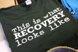 """it's a black T-shirt with white letters that say """"this is what recovery looks like"""""""