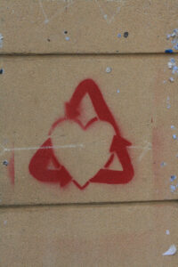 It's a painting of a recycling symbol around a heart in red paint on the side of a building