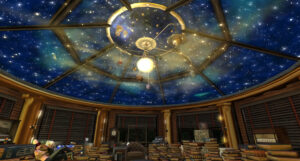a room that has a ceiling with stars on it and a mobile of the solar system hanging down
