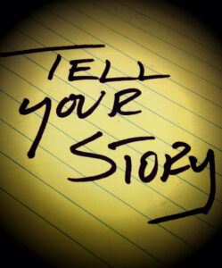 a yellow legal pad with the words tell your story written on it in black marker