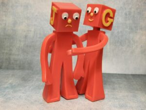 two toys; they are both red and look person-like but with big blocky heads. One has the letter J on its head in yellow and one has G on its head. G is comforting J who seems a little down.