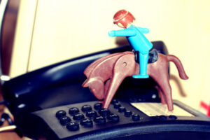 a phone with a toy rider on a horse atop it